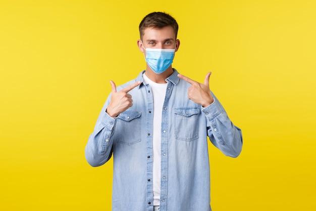 Concept van covid-19 pandemische uitbraak, levensstijl tijdens sociale afstand van het coronavirus. glimlachende knappe man die naar een medisch masker wijst, raad aan om het te dragen om te voorkomen dat je een virus oploopt.