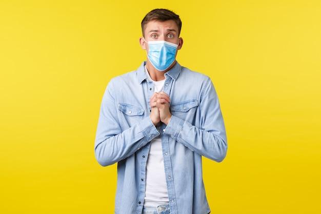 Concept van covid-19 pandemische uitbraak, levensstijl tijdens sociale afstand van het coronavirus. hoopvolle knappe man hand in hand in een smekend gebaar, smekend of biddend, met een medisch masker.