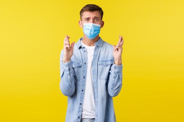 Concept van covid-19 pandemische uitbraak, levensstijl tijdens sociale afstand van het coronavirus. hoopvolle wanhopige blong-man met medisch masker, nerveus gekruiste vingers, veel geluk, in afwachting van belangrijk nieuws.