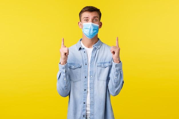 Concept van covid-19 pandemische uitbraak, levensstijl tijdens sociale afstand van het coronavirus. knappe blanke man met medisch masker die vraagt om omhoog te kijken, wijzende vingers naar de bovenste banner, gele achtergrond.
