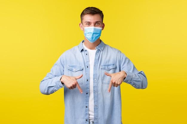 Concept van covid-19 pandemische uitbraak, levensstijl tijdens sociale afstand van het coronavirus. knappe tevreden mannelijke klant met medisch masker dat info toont, met de vingers naar beneden wijzend naar promo.