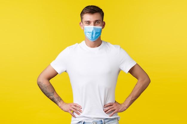 Concept van covid-19 pandemische uitbraak, levensstijl tijdens sociale afstand van het coronavirus. zelfverzekerde knappe slanke man met medisch masker en standaard wit t-shirt klaar voor werk, hand in hand op taille.