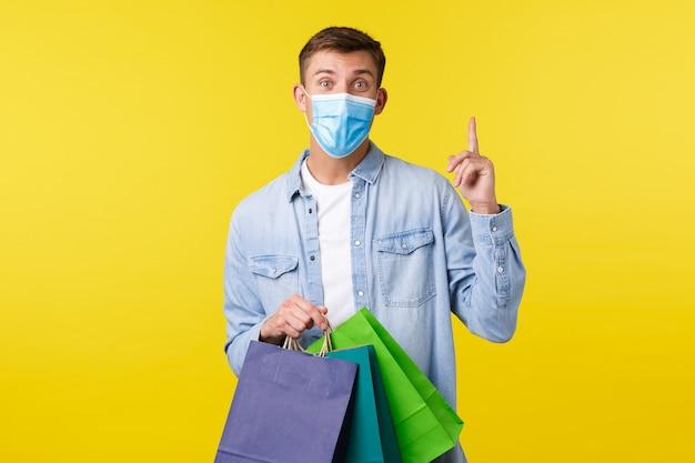 Concept van covid-19 pandemische uitbraak, winkelen en levensstijl tijdens coronavirus. jonge bedachtzame man met medisch masker, vinger omhoog, suggestie of idee, tassen uit de winkel vasthoudend.