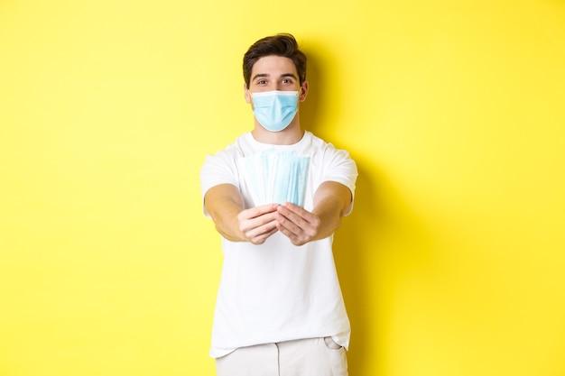 Concept van covid-19, quarantaine en preventieve maatregelen. jonge kaukasische mens die medische maskers voor u geeft, die zich tegen gele achtergrond bevindt.