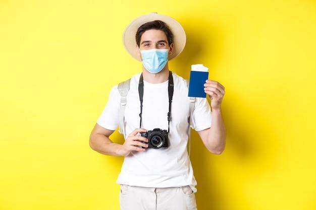 Concept van covid-19, reizen en quarantaine. gelukkige man toerist met camera, paspoort en kaartjes voor vakantie tonend, op reis gaan tijdens pandemie, gele achtergrond