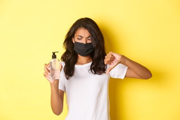 Concept van covid-19, sociale afstand en levensstijl. afbeelding van een teleurgestelde afro-amerikaanse vrouw met een gezichtsmasker, die duimen naar beneden laat zien en naar slechte handdesinfecterend middel kijkt, gele achtergrond