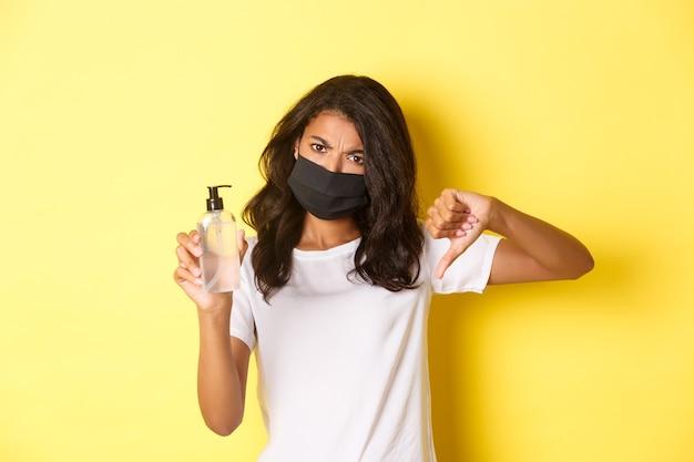 Concept van covid-19, sociale afstand en levensstijl. afbeelding van een teleurgestelde afro-amerikaanse vrouw met een gezichtsmasker, met duimen naar beneden, beveel geen slechte handdesinfecterend middel aan, gele achtergrond
