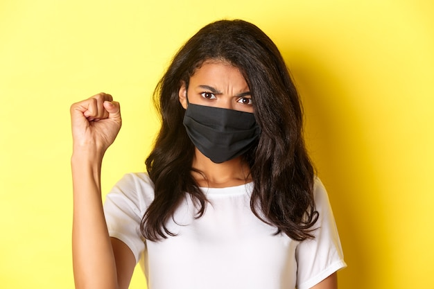 Concept van covid-19, sociale afstand en levensstijl. close-up van felle en zelfverzekerde afro-amerikaanse vrouw, die een demonstrant is in beweging van zwarte levens, een vuist toont, gezichtsmasker draagt