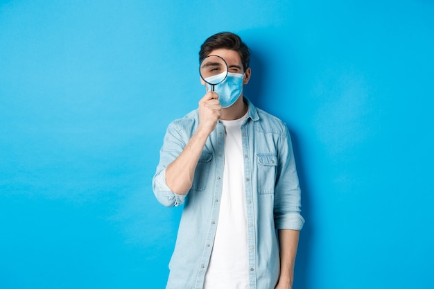 Concept van covid-19, sociale afstand en quarantaine. jonge man met medisch masker op zoek naar iets, kijkend door vergrootglas, staande tegen een blauwe achtergrond