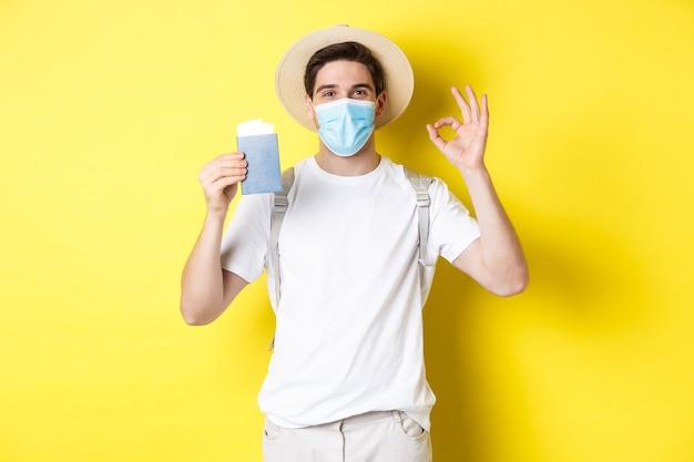 Concept van covid-19, toerisme en pandemie. gelukkige mannelijke toerist met medisch masker met paspoort, op vakantie gaan tijdens coronavirus, ok teken maken, gele achtergrond