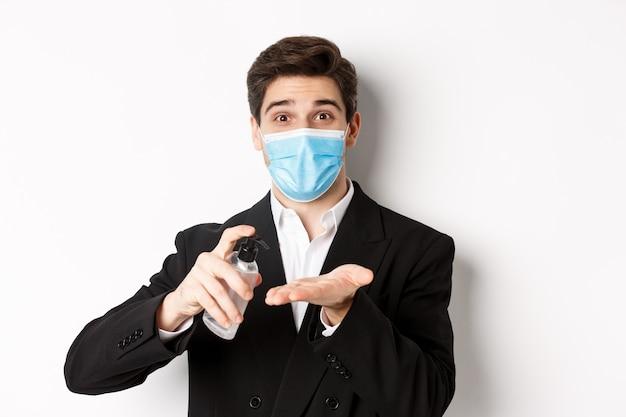 Concept van covid-19, zakelijke en sociale afstand. afbeelding van knappe zakenman in trendy pak en medisch masker, handen reinigen met handdesinfecterend middel, staande op witte achtergrond.