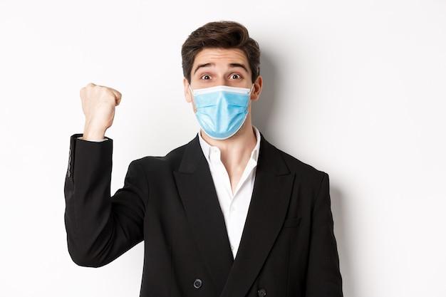 Concept van covid-19, zakelijke en sociale afstand. close-up van vrolijke zakenman in medisch masker en pak, vreugde, doel bereiken en vieren, staande op witte achtergrond