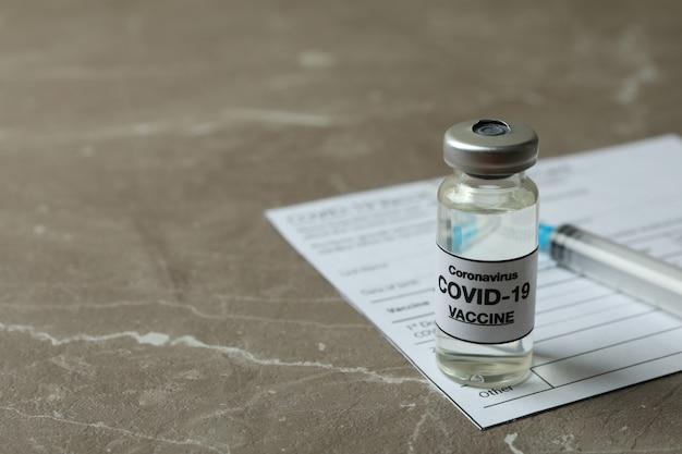 Concept van covid - vaccinatie 19 met vaccin en spuit op grijze gestructureerde achtergrond