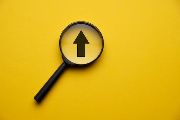 Concept van creativiteit en groei van bedrijfsontwikkeling - vergrootglas met een zwarte pijl op een gele ruimte.