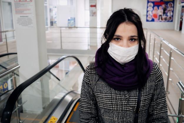 Concept van de coronovirus covid-19-epidemie. jong europees meisje in een medisch masker