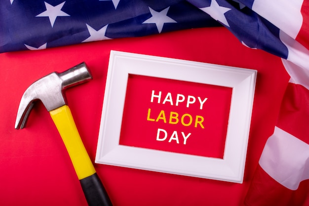Concept van de dag van de arbeid de vs, hamer, en wit kader op rode document achtergrond met vlag van de vs