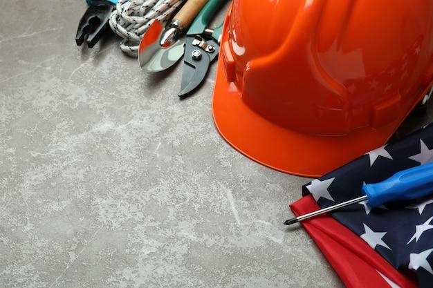 Concept van de dag van de arbeid met verschillende bouwhulpmiddelen op grijze gestructureerde achtergrond
