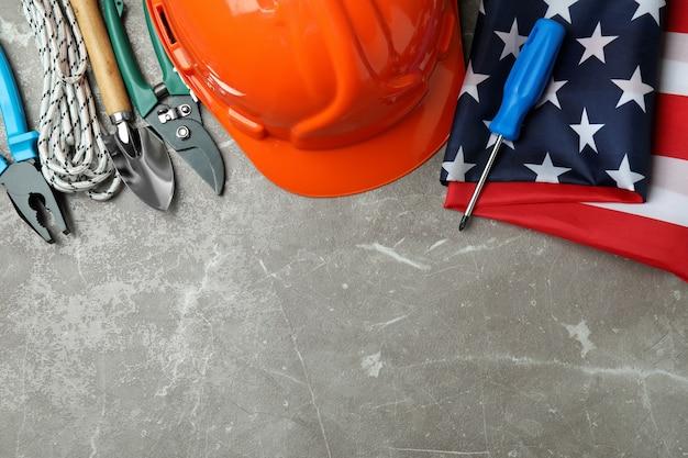 Concept van de dag van de arbeid met verschillende bouwhulpmiddelen op grijze textuur