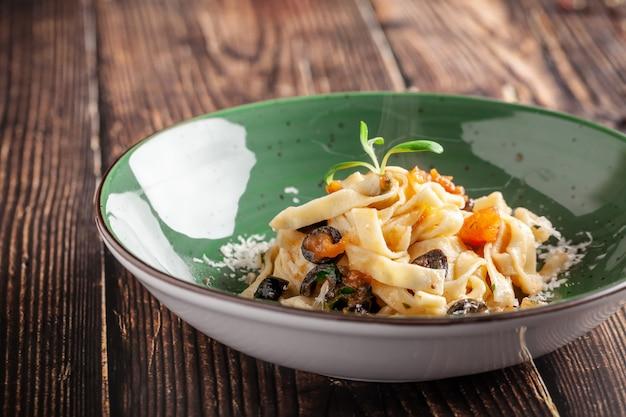 Concept van de italiaanse keuken. tagliatelle met groenten, tomaten, olijven en parmezaanse kaas. versierd met peterselie. dienende schotels in een restaurant in een groene plaat. kopie ruimte