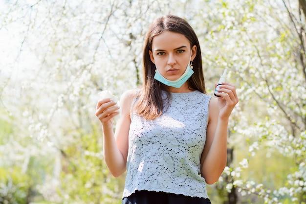 Concept van de lente ziekte. jonge vrouw in medische masker met servetten en spray voor haar allergie of koorts, koude en lopende neus