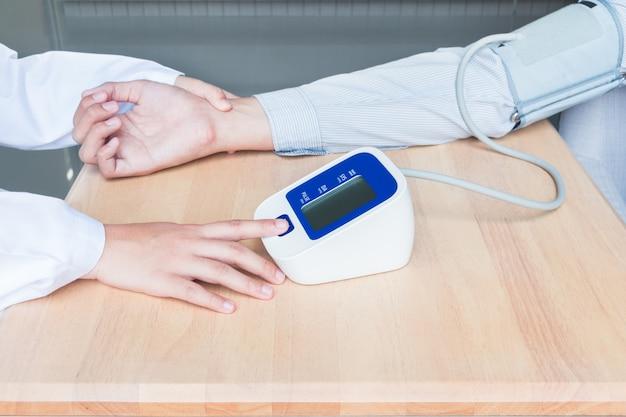 Concept van de startknop van de vrouwelijke arts druk op de bloeddruk