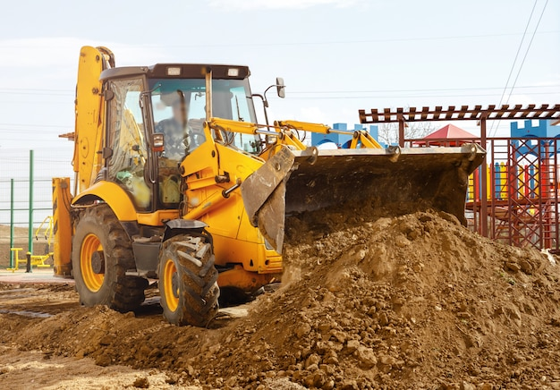 Concept van de tractor, de tractor graaft en begraaft een greppel