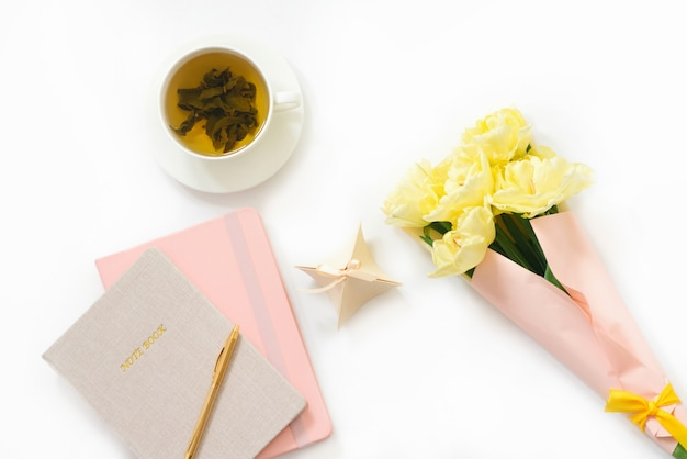 Concept van de werkplek van een vrouw van een freelancer of blogger. notebooks, een pen, een bos gele lentetulpen, een kopje groene thee op een witte achtergrond. ochtend thuis werkplek