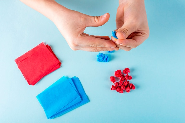 Concept van doe-het-zelf en de creativiteit van kinderen. de handen van het kind verfrommelen stukjes gekleurd papier. valentijnsdag ambacht.