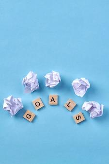 Concept van doel. houten blokken met letters en stukjes papier. geïsoleerd op blauwe achtergrond.