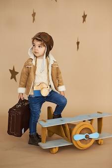 Concept van dromen en reizen. piloot vlieger kind met een stuk speelgoed vliegtuig en koffer speelt in een beige