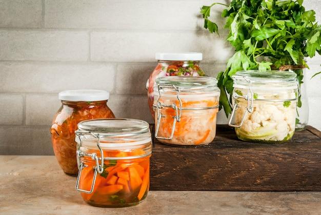 Concept van een gefermenteerde maaltijd. thuis ingeblikt voedsel en knuppels. veganistisch eten. groenten. blikken salsa in blik, zuurkool, gemarineerde wortelen, kimchi en bloemkoolbroccoli. home keukentafel. copyspace
