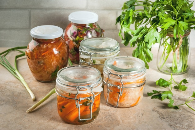 Concept van een gefermenteerde maaltijd. thuis ingeblikt voedsel en knuppels. veganistisch eten. groenten. blikken salsa in blik, zuurkool, gemarineerde wortelen, kimchi en bloemkoolbroccoli. home keukentafel.