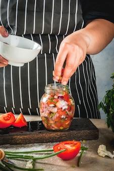 Concept van een gefermenteerde maaltijd. thuis ingeblikt voedsel en knuppels. veganistisch eten. groenten. persoonsvrouw die eigengemaakte mexicaanse salsasaus koken. blikken met behoud, zuurkool, wortelen, greens, uien.