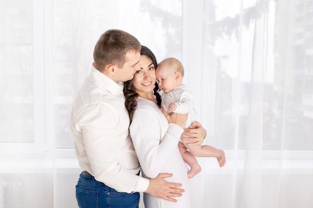 Concept van een gelukkig jong gezin, levensstijl, ouders met een pasgeboren baby in hun armen
