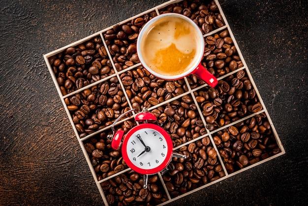 Concept van een vrolijke, goede start van de dag, ochtendkoffie. donker roestig oppervlak met koffiebonen, een wekker en een kopje koffie. bovenaanzicht kopie ruimte