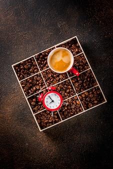 Concept van een vrolijke, goede start van de dag, ochtendkoffie. donkere roestige achtergrond met koffiebonen, een wekker en een kopje koffie. bovenaanzicht kopie ruimte