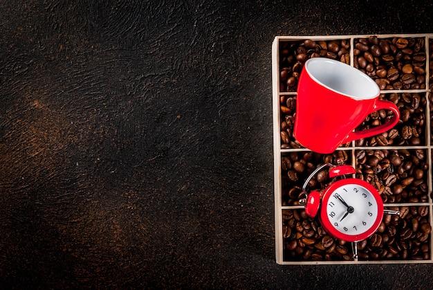Concept van een vrolijke, goede start van de dag, ochtendkoffie. koffiebonen, een wekker