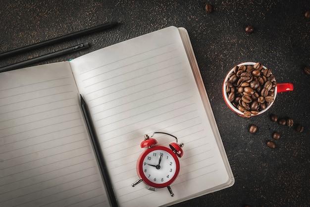 Concept van een vrolijke, goede start van de werkdag, 's ochtends koffie. donkere roestige achtergrond met koffiebonen, wekker, blocnote en een kopje koffie. bovenaanzicht kopie ruimte