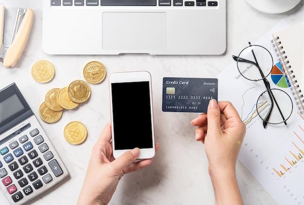 Concept van een vrouw die online betaling doet met kaart en smartphone geïsoleerd op een moderne marmeren kantoortafel, mock up, bovenaanzicht, kopie ruimte, plat leggen, close-up