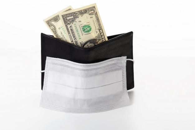 Concept van een wereldwijde crisis en dalende inkomens als gevolg van pandemisch coronavirus covid-19. portemonnee met een dollar en een beschermend masker geïsoleerd.