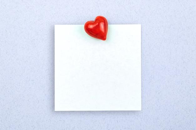 Concept van eenvoudige liefdesbrief, vastgemaakt notitieboekje met rood hart op een lichtblauwe achtergrond, kopieer ruimtefoto