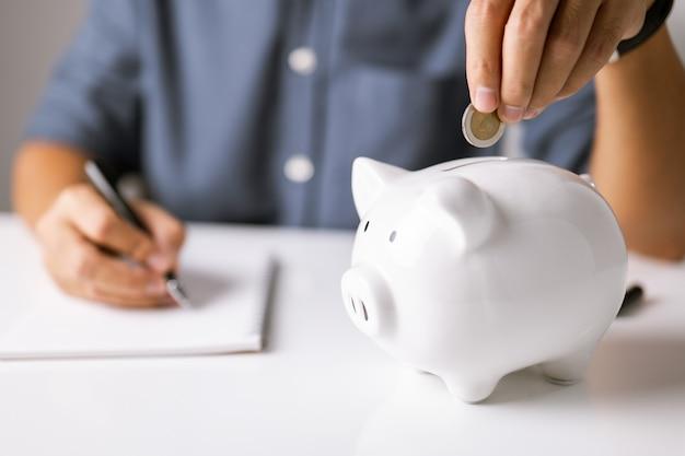 Concept van financiële geletterdheid bedrijfsinvesteringen en planning mannenhand zet munt in spaarvarken
