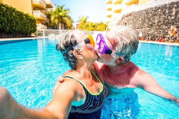 Concept van geen limiet leeftijd en relatie met een paar blanke gelukkige senior oude mensen die samen zoenen in het zwembad met plezier tijdens de zomervakantie vakantie