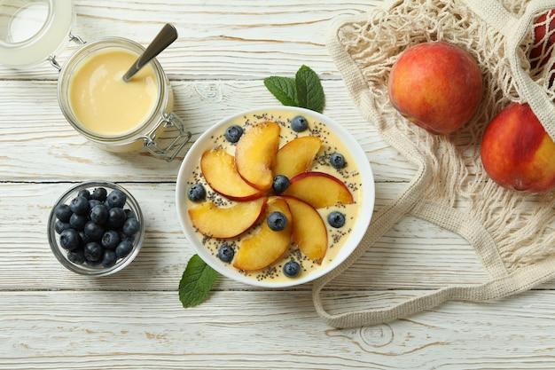 Concept van gezond voedsel met perzikyoghurt op witte houten tafel