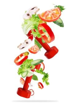 Concept van gezonde levensstijl. sportuitrusting met groenten vliegen geïsoleerd op wit