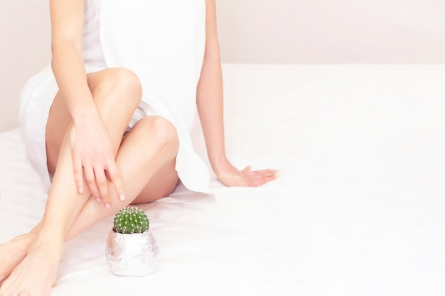 Concept van gladde mooie huid zonder extra haar. een mooi meisje zit en kijkt naar een cactus. ontharing. nee tegen haar. copyspace. plaats uw tekst