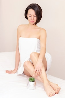 Concept van gladde mooie huid zonder extra haar. een mooi meisje zit en kijkt naar een cactus. ontharing. nee tegen haar