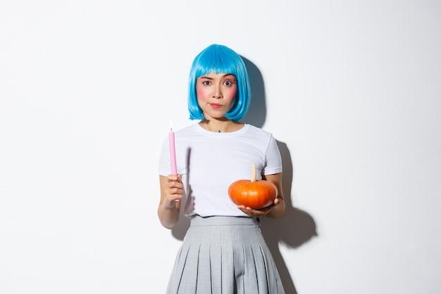 Concept van halloween. afbeelding van aantrekkelijk sceptisch aziatisch meisje in blauwe pruik