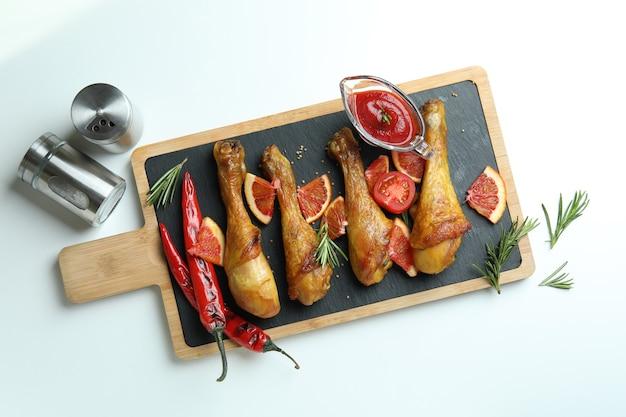 Concept van heerlijk eten met bord van gebraden kip drumsticks op witte achtergrond
