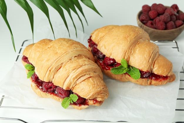 Concept van heerlijk eten met croissants met frambozenjam op witte achtergrond